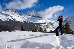 Female nature photographer taking picture of the snowy mountains at the Icefields Parkway in Jasper National, Alberta, Canada. Full length photo of a caucasian stock image