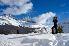 Female nature photographer taking picture of the snowy mountains at the Icefields Parkway in Jasper National, Alberta, Canada. Full length photo of a caucasian stock photos