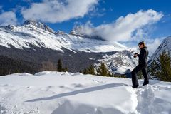 Female nature photographer taking picture of the snowy mountains at the Icefields Parkway in Jasper National, Alberta, Canada. Full length photo of a caucasian royalty free stock photography