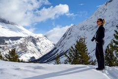 Female nature photographer taking picture of the snowy mountains at the Icefields Parkway in Jasper National, Alberta, Canada. Full length photo of a caucasian stock photo