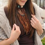 Female neck with brown leather boho necklace and ear with red feathers earrings, handmade jewelry. Female neck with brown leather boho necklace, handmade jewelry royalty free stock image