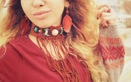 Female neck and ears with boho necklace and earrings with red feathers and brown leather, handmade jewelry Royalty Free Stock Photography