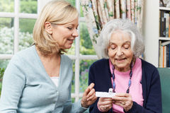 Female Neighbor Helping Senior Woman With Medication stock image