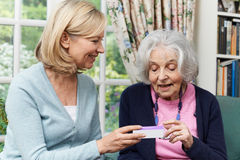 Female Neighbor Helping Senior Woman With Medication Royalty Free Stock Photos
