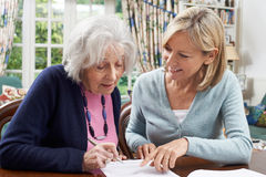 Female Neighbor Helping Senior Woman To Complete Form Royalty Free Stock Photography