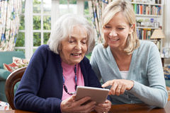 Female Neighbor Showing Senior Woman How To Use Digital Tablet Royalty Free Stock Images