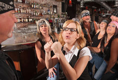 Female Nerd Confronting Man in Bar. Female geek puts up fist to tough men in bar Stock Photos
