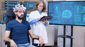 Female neurologist reading data from brainwave scanning headset