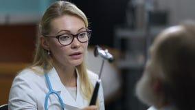 Female neurologist testing reflexes of eye of patient stock footage