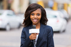 Female news reporter. Happy female african news reporter working outdoors Stock Photo