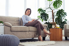 Female with nice smile working in laptop while sitting on sofa Stock Photos