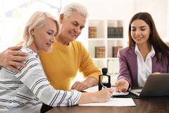 Female notary working with mature couple