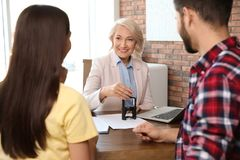 Female notary working with young couple