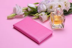 female notepad and perfume next to the flowers of eustoma on a bright pink background stock photography