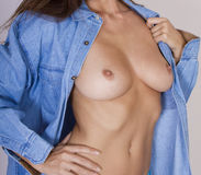 Female nude breasts wearing denim shirt Royalty Free Stock Photography
