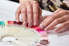 Female nude manicure with black lace. Beautiful female finger nails with beige nail on nail samples. Hands and nail care Stock Images