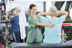 Female Nurse Assisting Senior Woman In Back Exercise Royalty Free Stock Photography