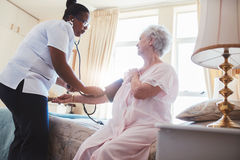 Female nurse checking blood pressure of a senior woman. Female nurse checking blood pressure of a senior women sitting on bed at home. Home carer checking royalty free stock image