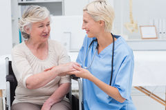 Female nurse checking flexibility of patients wrist. Smiling female nurse checking flexibility of patients wrist in clinic Stock Image