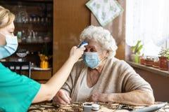 Free Female Nurse Checking Temperature To Senior Woman During Home Visit Stock Image - 213479671