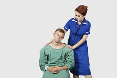 Female nurse consoling male patient against gray background Stock Photography