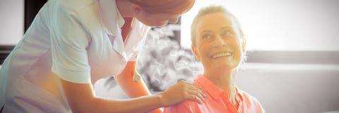 Female nurse consoling senior woman. Female nurse consoling senior women at home royalty free stock images