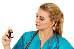 Female nurse or doctor holding medicine bottle in the hand.  Stock Image