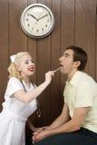 Female nurse examinating man's mouth. royalty free stock photos