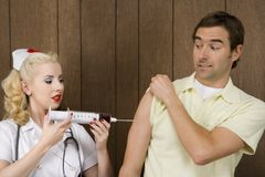 Female nurse giving man shot with giant syringe. Royalty Free Stock Photography