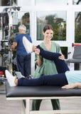 Female Nurse Helping Senior Woman In Leg Exercise Royalty Free Stock Images