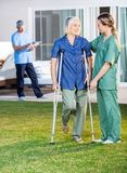Female Nurse Helping Senior Woman To Use Crutches. Female nurse helping senior women to use crutches with caretaker in background at nursing home lawn Royalty Free Stock Images