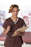 Female nurse holding a clipboard and stethoscope. Pretty woman in scrubs holding charts and a stethoscope Royalty Free Stock Photography