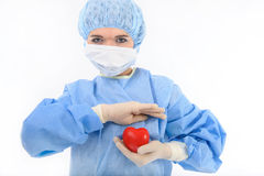 Female nurse holding a heart. Female nurse or doctor in sterile blue garment and gloves holding a heart in protective position royalty free stock photography