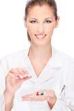 Female nurse holding  medics. Pretty female nurse holding  medicals, isolated on white Stock Photography