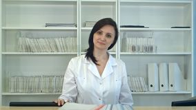 Female nurse at hospital reception looking at camera. Professional shot in 4K resolution. 097. You can use it e.g. in your commercial video, business, medicine stock images