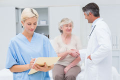 Female nurse making reports while doctor and patient shaking hands Stock Photography