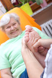 Female Nurse massaging foot of a patient Stock Photos