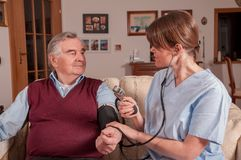 Nurse measuring blood pressure with sphygmomanometer royalty free stock photos