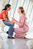 Female Nurse Offering Counselling To Depressed Woman. Smiling Royalty Free Stock Photography