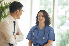 Female nurse and patient talking and smiling in the hospital Royalty Free Stock Photography