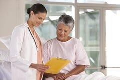 Female nurse performing checkup Stock Photo