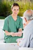 Female Nurse Playing Cards With Senior Man stock photo