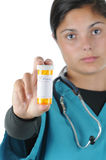 Female nurse with Prescription Bottle. Female medical professional holding out a prescription bottle isolated over white. Shallow depth of field with focus on Stock Photo