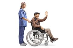 Female nurse pushing a senior patient sitting in a wheelchair and greeting with hand. Full length profile shot of a female nurse pushing a senior patient sitting stock photography