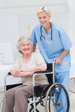 Female nurse pushing senior patient in wheelchair royalty free stock photo