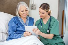 Female Nurse And Senior Woman Using Tablet PC Stock Photo