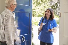Female nurse showing ID to senior man at his front door stock photo