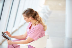 Female Nurse Sitting In Chair Using Digital Tablet Royalty Free Stock Images