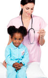Female nurse taking little girl's temperature Royalty Free Stock Photos