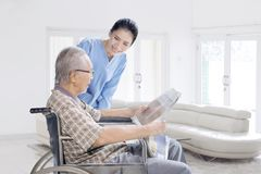 Female nurse talking with old man at home stock images